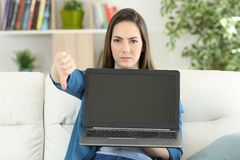 Anwry woman showing a blank laptop screen. Sitting on a couch in the living room at home royalty free stock photo