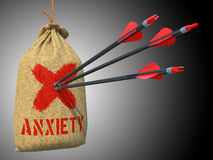 Anxiety - Arrows Hit in Target. Anxiety - Three Arrows Hit in Red Mark Target on a Hanging Sack on Grey Background Stock Photography