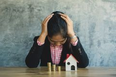 Anxiety businesswoman with model house and coins on desk. Concept saving and protect  housing Royalty Free Stock Images