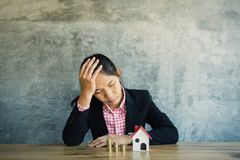 Anxiety businesswoman with model house and coins on desk. Concept saving and protect  housing Stock Images