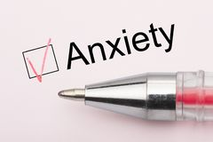 Anxiety - checkbox with a tick on white paper with pen. Checklist concept stock photography