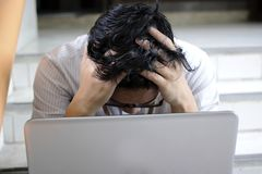 Anxiety confused young Asian business man with laptop covering face with his hands.  Stock Photo