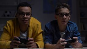 Anxious African-American and European guys playing video game, procrastinators
