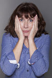Anxious attractive mature woman hiding her cheeks Royalty Free Stock Photos