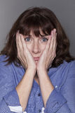 Anxious attractive mature woman hiding her face Royalty Free Stock Images