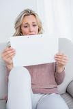 Anxious blonde on couch holding page Stock Image