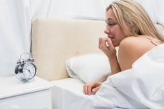Anxious blonde looking her alarm clock Stock Photos