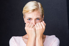 Anxious blonde woman looking at camera. On black background Royalty Free Stock Image