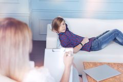Anxious boy lying on couch in psychologist office. Teenage problems. Male youngster in casual attire relaxing on a sofa and looking at a professional doctor Stock Image