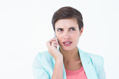 Anxious brunette on the phone. On white backround stock photography