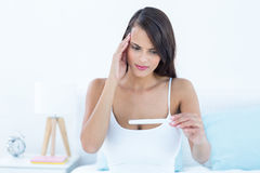 Anxious brunette woman looking her pregnancy test Royalty Free Stock Photography