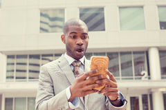 Anxious business man looking at phone seeing bad news with disgusting shocked face expression. Closeup portrait anxious young business man looking at smart phone Royalty Free Stock Images