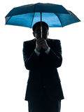 Anxious business man under umbrella silhouette. One caucasian anxious business man under umbrella in silhouette studio isolated on white background royalty free stock photo