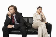 Anxious businessman and businesswoman sitting on sofa, cut out Stock Photo