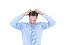 Anxious businessman with hands on his head. Anxious white hair businessman against a white screen Stock Photo