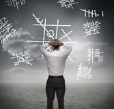 Anxious businessman losing at noughts and crosses. With hands on head Stock Image