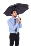 Anxious businessman sheltering with umbrella Royalty Free Stock Image
