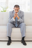 Anxious businessman sitting on couch Stock Photography
