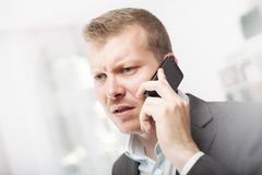 Anxious businessman taking a mobile call Royalty Free Stock Photography