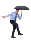 Anxious businessman under umbrella balancing Stock Image