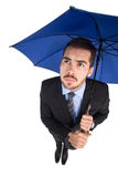 Anxious businessman under umbrella looking up Royalty Free Stock Photos