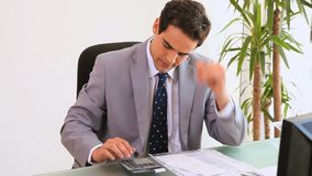 Anxious businessman using a calculator. At his desk stock footage
