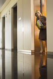 Anxious businesswoman exiting office elevator, looking nervously down corridor, surface level Royalty Free Stock Images