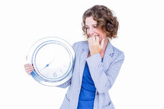 An anxious businesswoman holding clock. On white background Royalty Free Stock Photography