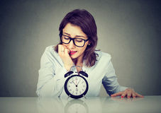 Anxious businesswoman looking nervously at alarm clock. Anxious young business woman looking nervously at alarm clock Stock Images