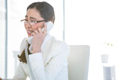 Anxious businesswoman using landline. At her desk Stock Images