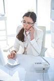 Anxious businesswoman using landline. At her desk Royalty Free Stock Images