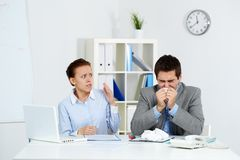 Anxious about catching flu. Image of sick businessman sneezing while anxious female looking at him in office Stock Images