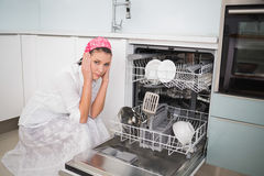 Anxious charming woman sitting next to dish washer Royalty Free Stock Photos