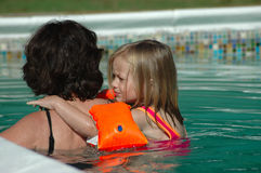 Anxious child. A little blond toddler girl child with anxious expression in the face learning how to swim embracing grandma in the swimmingpool outdoors in the Stock Photos