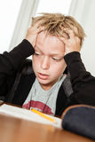 Anxious child struggling to complete homework. Single anxious blond boy in black sweater holding his head in frustration and desperation as he struggles to Stock Photo