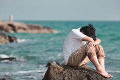 Anxious confused Asian man covering face with hands and bend down head on the rock of sea shore. Anxious confused Asian man covering face with hands and bend royalty free stock image