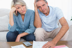 Anxious couple going over bills looking at camera. At home in living room Stock Image