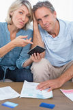 Anxious couple going over their debt looking at camera Stock Photos