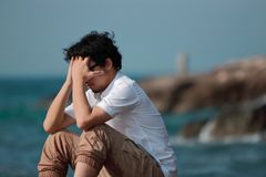Anxious depressed Asian man covering face with hands and bend down head.  Stock Photo