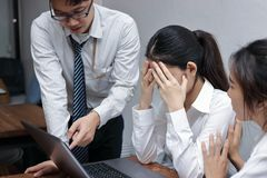 Anxious depressed young Asian business women are being blamed with boss in workplace. Stock Images