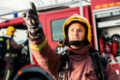 Anxious fireman pointing at fire. Anxious fireman with fire truck in background pointing at danger situation Royalty Free Stock Photos