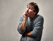 Anxious insecure man. Insecure worried mature man portrait over gray background Stock Image