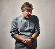 Anxious insecure man. Insecure worried mature man portrait over gray background Stock Photo