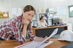 Anxious lady looking at paperwork stock photos