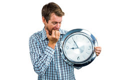 Anxious late man holding a clock. On white background Royalty Free Stock Photos