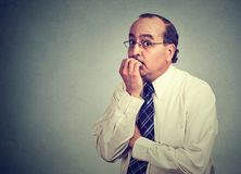 Anxious male worker biting nails stock photography