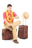 Anxious man checking the time seated on a bag Royalty Free Stock Photos