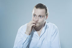 Anxious man chewing on fingernails Stock Photo