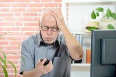 An anxious man looks at his smartphone Stock Photos