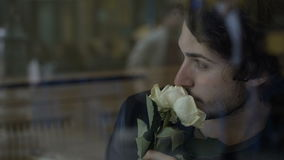 Anxious man in love waiting for girlfriend with flowers sitting by a window in a pub. Anxious young man in love waiting for girlfriend with flowers sitting by a stock video